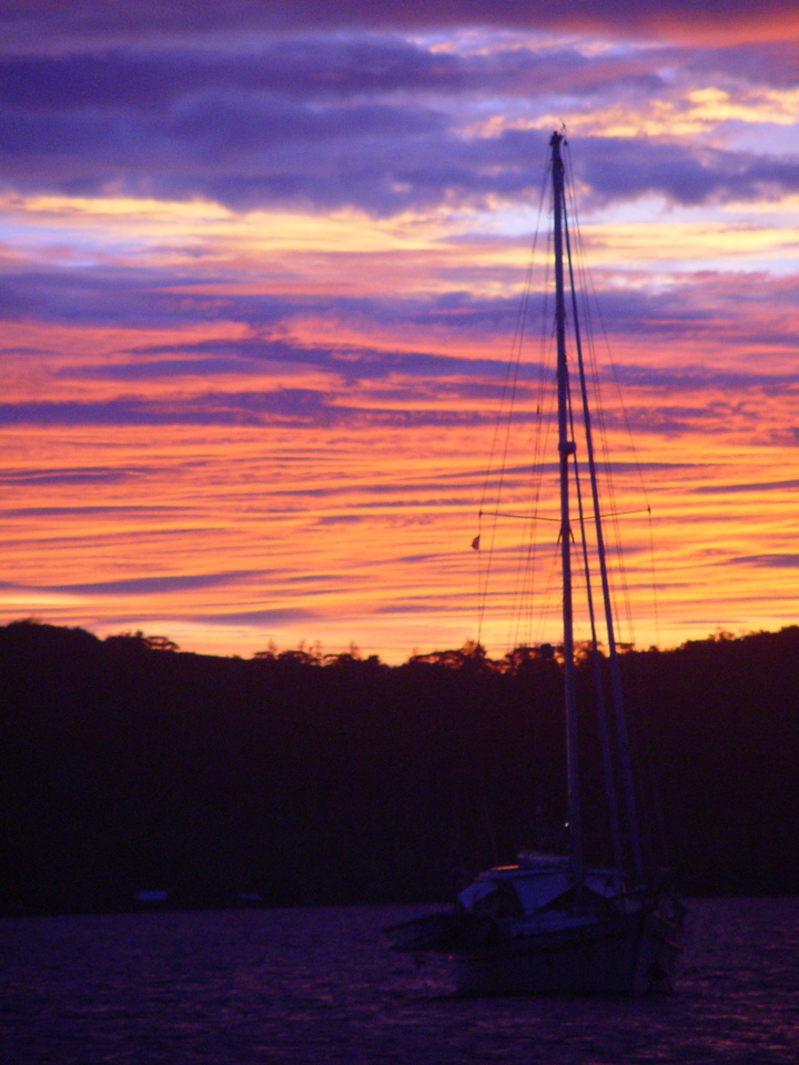 A sailboat rests at anchor against burnt orange and purple clouds at sunset - Dana Sisson